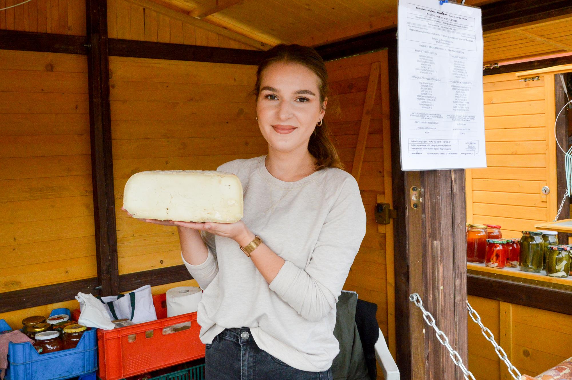 """Agata Marczinska z Borucina sprzedaje sery kozie. Jej rodzice wyrabiają je z mleka kóz anglonubijskich. Mleko tych kóz jest pozbawione charakterystycznego zapachu, dzięki czemu wytwarzane z niego sery mają przyjemny, łagodny zapach. """"Zagroda na pograniczu"""" w Borucinie liczy 150 kóz anglonubijskich. Na zdjęciu Agata Marczinska trzyma w rękach ser kozi długodojrzewający."""