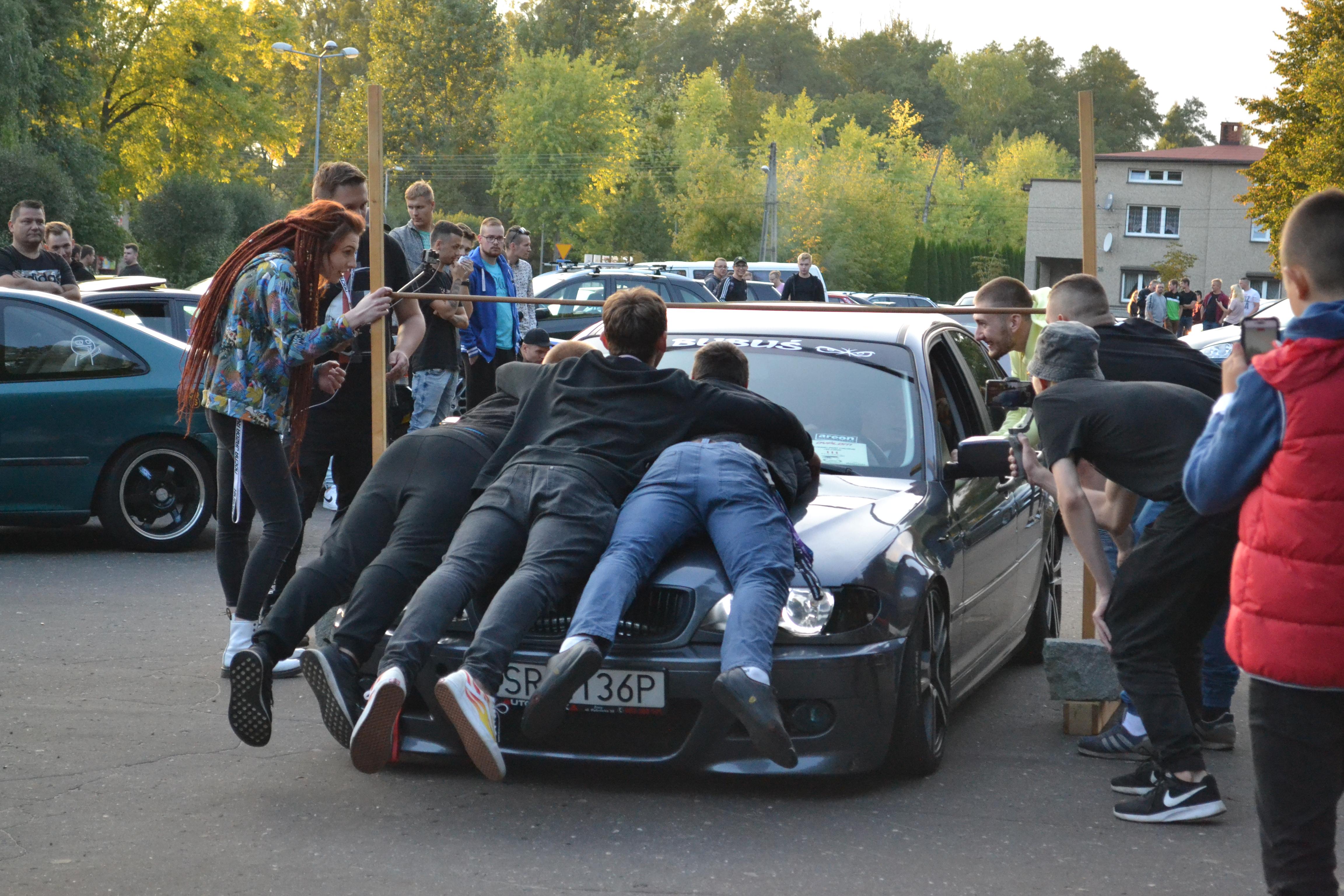 """Niektórzy uczestnicy car limbo kładli się na maskach, by """"zniżyć"""" samochód"""